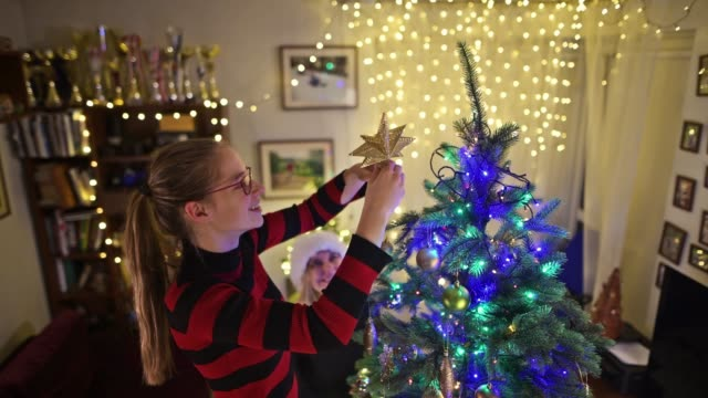teenage girl and mother decorating the christmas tree - imgorthand stock videos & royalty-free footage