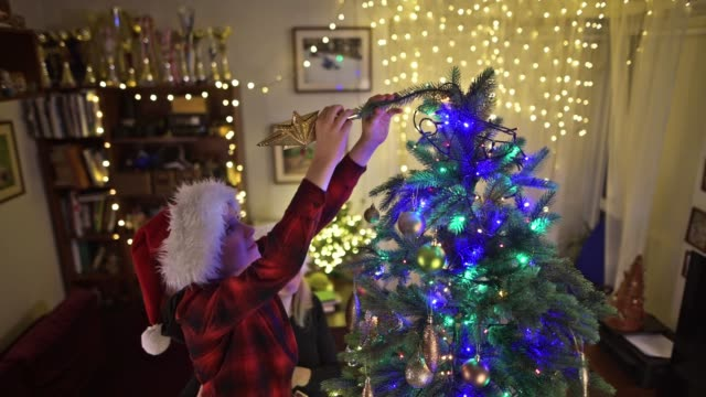 teenage girl and mother decorating the christmas tree - decorating the christmas tree stock videos & royalty-free footage