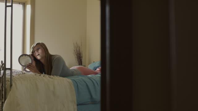 vidéos et rushes de ws pan teenage (16-17) girl applying make up on bed, american fork, utah, usa - quête de beauté