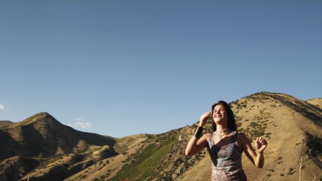 MS TU SLO MO Teenage girl (16-17) bouncing giant inflatable globe ball standing in field / South Fork, Utah, USA