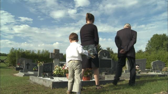 ms teenage girl (12-13), boy (4-5) and senior man visiting tombstone at cemetery, latour, belgium - friedhof stock-videos und b-roll-filmmaterial