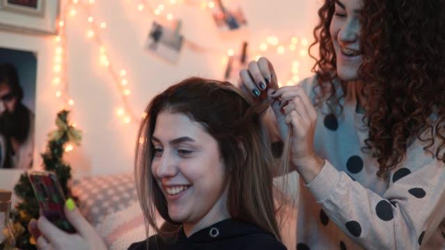 teenage girl braiding her friend's hair - slumber party stock videos & royalty-free footage
