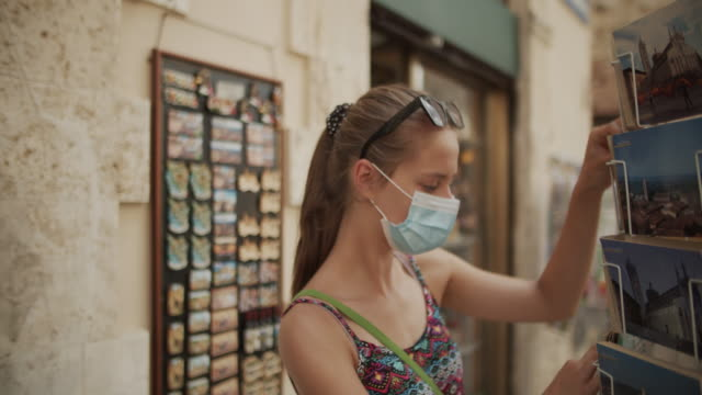 teenage girl buying postcards at street stand - souvenir stock videos & royalty-free footage