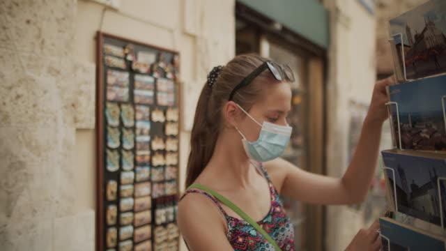 ストリートスタンドではがきを買う10代の少女 - お土産点の映像素材/bロール