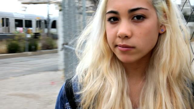 Teenage girl chews gum waits by train