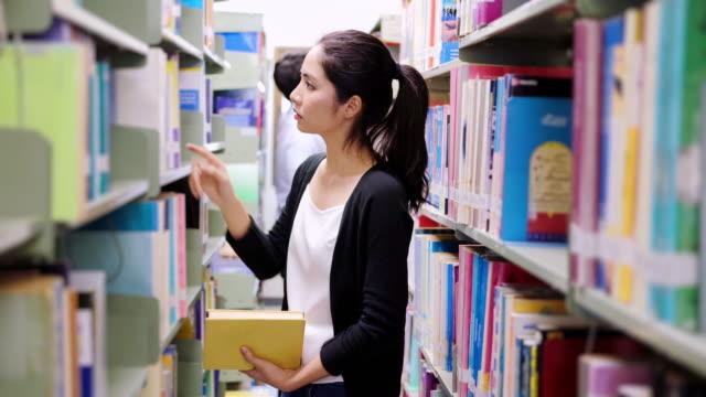 vídeos de stock e filmes b-roll de teenage girl choosing a book in the library. - arquivista