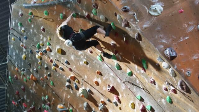 teenage girl climbing on an indoor climbing wall