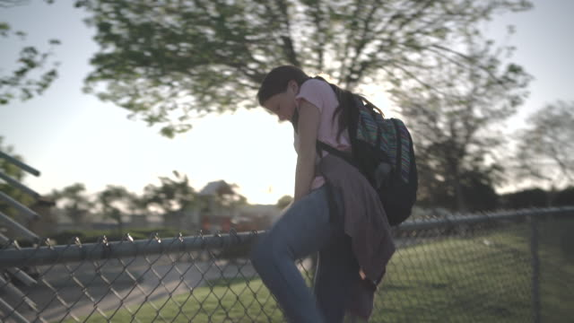 vídeos de stock, filmes e b-roll de ws teenage girl climbing over a chainlink fence - cerca