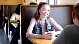 Teenage girl conversing with boyfriend in coffee shop