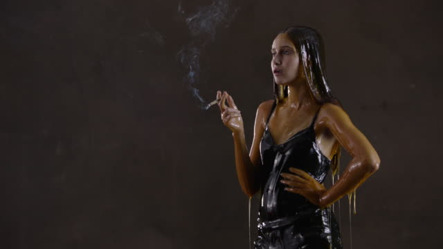 teenage girl covered in honey smokes cigarette, slow motion - sensory perception stock videos & royalty-free footage
