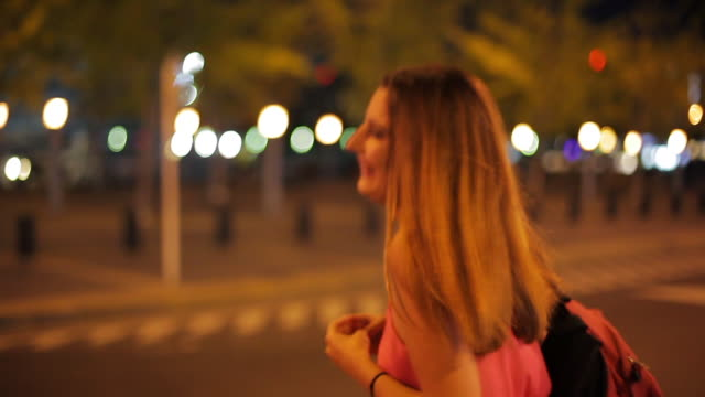 teenage girl crossing street and smiling cheerfully at night - weiblicher teenager allein stock-videos und b-roll-filmmaterial