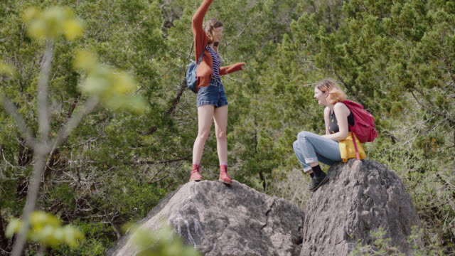 Teenage girl dances on top of mountain with earbuds in as sister laughs.