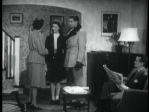 vídeos de stock e filmes b-roll de b/w 1947 teenage girl + date say goodbye to parents in living room + exit - sentar se