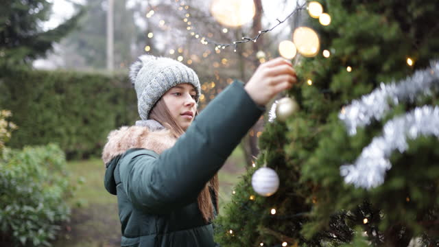 teenage girl decorating christmas tree in the back yard - one teenage girl only stock videos & royalty-free footage