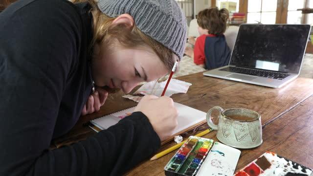 vídeos y material grabado en eventos de stock de teenage girl doing a watercolor picture - sólo una adolescente