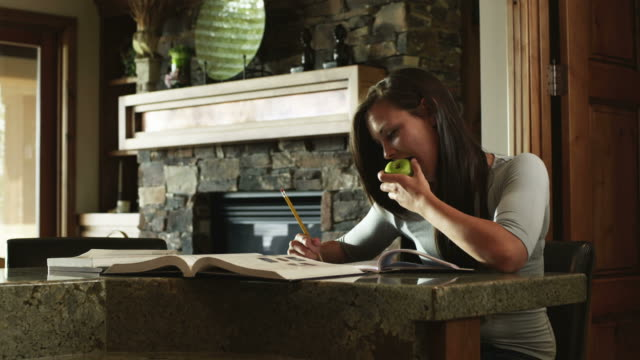 ms ds teenage (16-17) girl doing homework and eating apple at home, american fork, utah, usa - one teenage girl only stock videos & royalty-free footage
