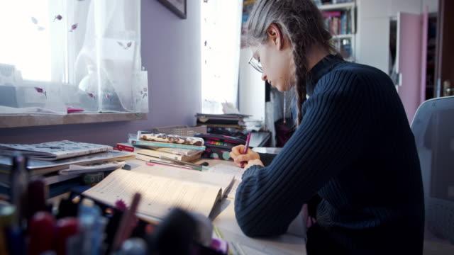 vidéos et rushes de adolescente faisant des devoirs à la maison - jeunes filles