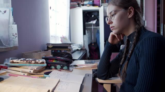 vídeos de stock e filmes b-roll de teenage girl doing homework at home - esforço