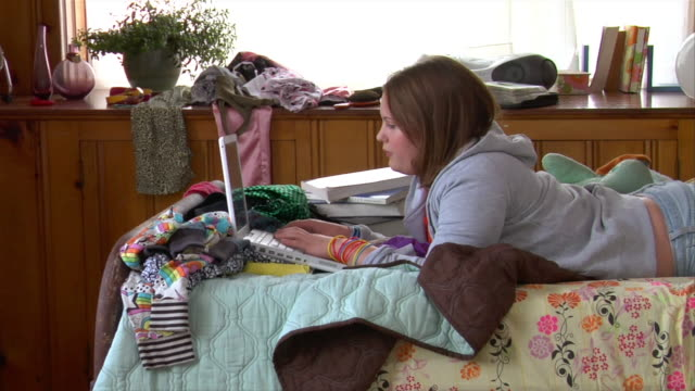 vidéos et rushes de cu zo teenage girl doing homework on bed with laptop - messy bedroom