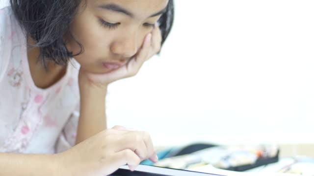 vidéos et rushes de adolescente faisant des devoirs utilisant le téléphone intelligent - une seule adolescente