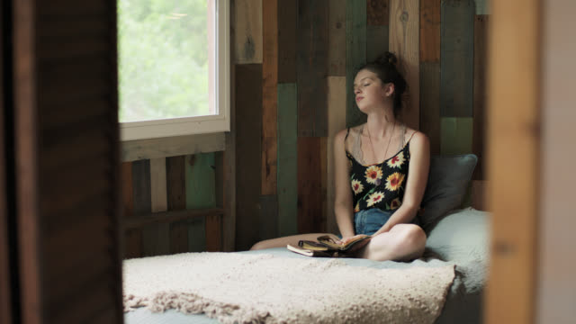 WS SLO MO. Teenage girl dozes and daydreams in rustic treehouse bedroom.