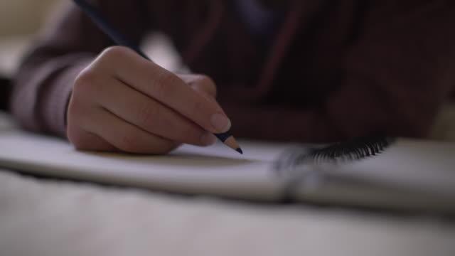 CU teenage girl drawing in her bedroom
