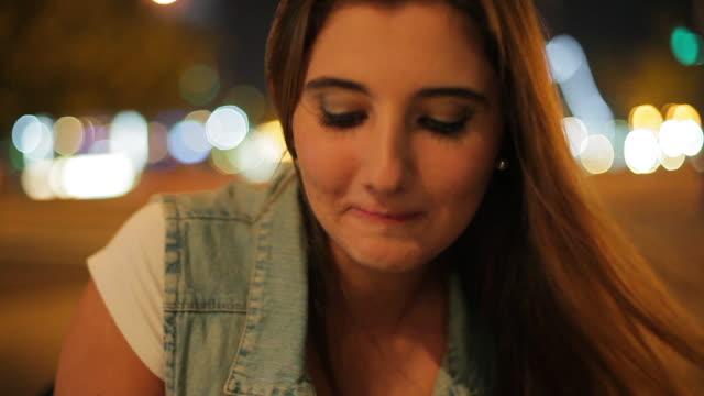 teenage girl drinking coffee outdoors at night - プエルトマデロ点の映像素材/bロール