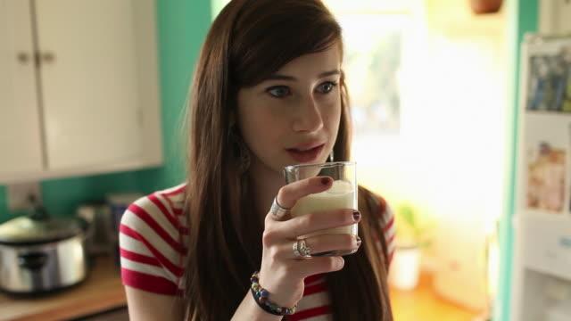 vídeos de stock e filmes b-roll de teenage girl drinking glass of milk - só meninas adolescentes
