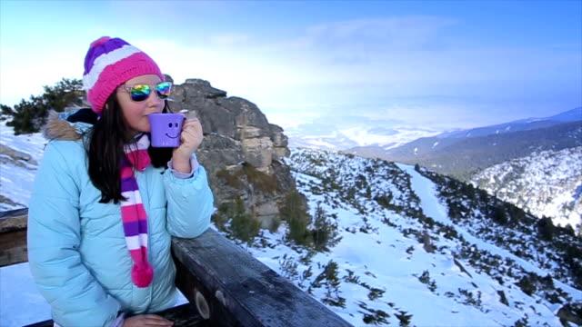 Teenage girl drinking tea on the top of the mountain