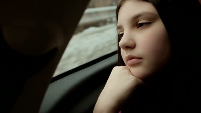 Teenage girl driving in the car on back seat,winter vacation