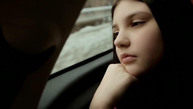 Adolescente au volant de la voiture sur la banquette arrière, vacances d'hiver