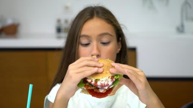 teenage girl eating cheeseburger - cheeseburger stock videos & royalty-free footage