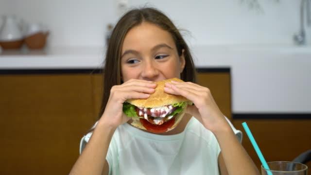 tonårig flicka äter ostburgare - endast en tonårsflicka bildbanksvideor och videomaterial från bakom kulisserna