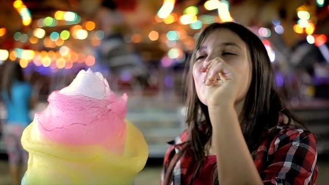 vídeos de stock, filmes e b-roll de adolescente comendo algodão doce no parque de diversões - comida doce