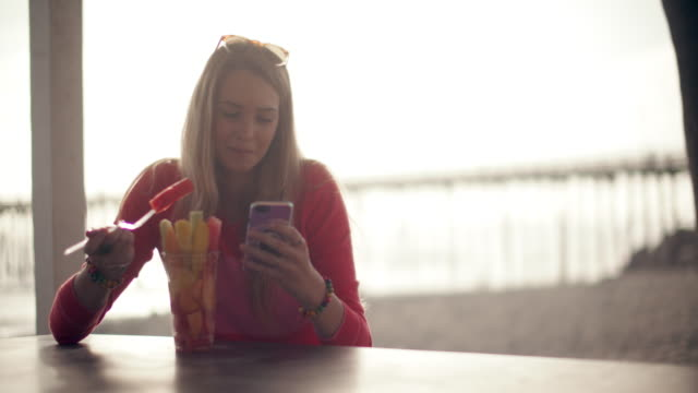 ms teenage girl eating fruit and texting at the beach - long hair stock videos & royalty-free footage