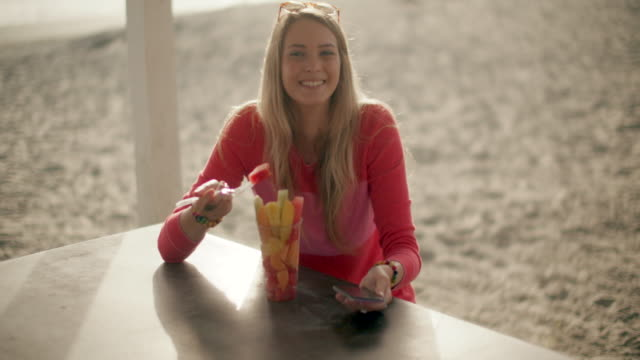 vídeos de stock e filmes b-roll de ws teenage girl eating healthy at the beach - fruta