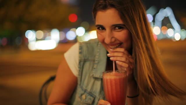 vídeos y material grabado en eventos de stock de teenage girl enjoying drink outdoors at night portrait - cóctel tropical