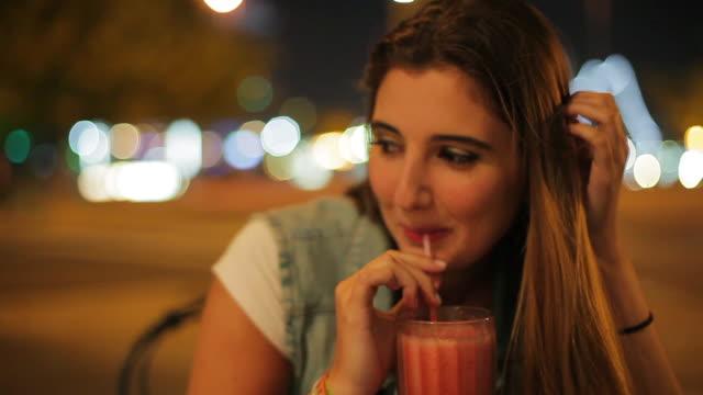 vídeos y material grabado en eventos de stock de teenage girl enjoying drink outdoors at night - cóctel tropical