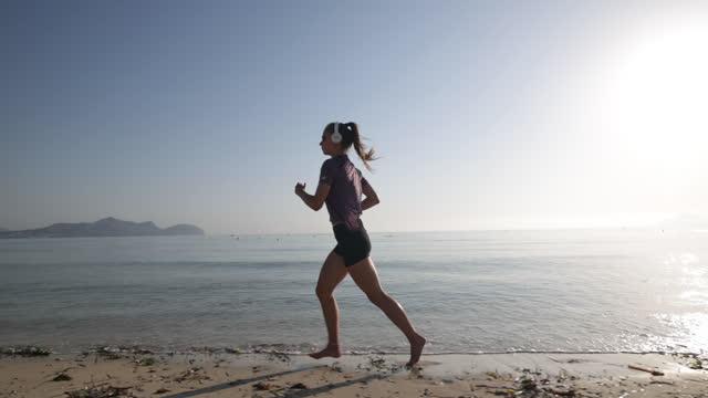 vídeos de stock, filmes e b-roll de adolescente curtindo correr pelo mar pela manhã - só uma adolescente menina