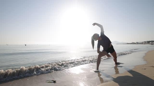 vídeos de stock, filmes e b-roll de adolescente curtindo se alongando pelo mar pela manhã - só uma adolescente menina