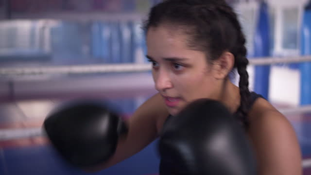 teenage girl exercising in boxing ring, training with coach - kickboxing stock videos & royalty-free footage