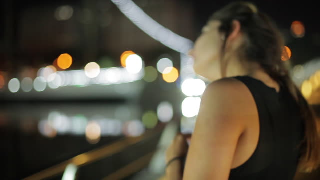 vídeos y material grabado en eventos de stock de teenage girl fixing hair absentmindedly while looking at view from pier at night - sólo una adolescente