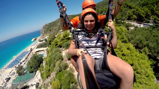 teenage  girl flying on a paraglider with an instructor - tourism stock videos & royalty-free footage