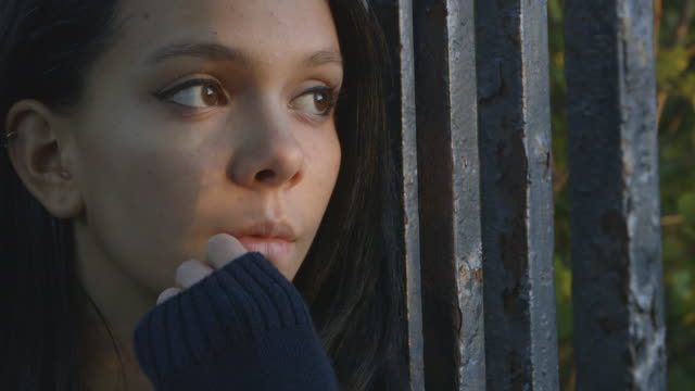 a teenage girl gazing through a fence - hand am kinn stock-videos und b-roll-filmmaterial