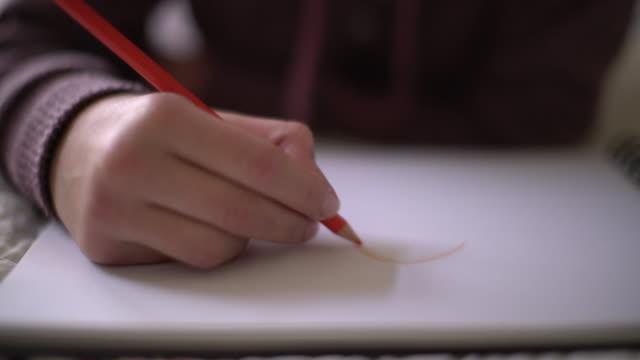cu teenage girl hand drawing on a piece of paper - weiblicher teenager allein stock-videos und b-roll-filmmaterial