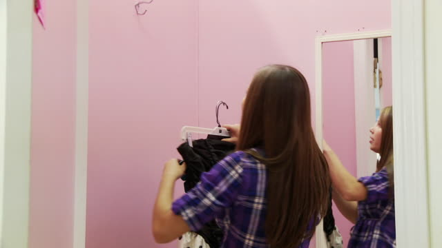 ms teenage girl (16-17) hanging up dresses on hook in fitting room / morris, illinois, usa - pacific islander girl stock videos & royalty-free footage