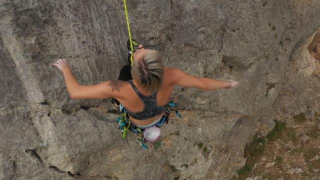 vídeos y material grabado en eventos de stock de chica adolescente divirtiéndose mientras escala la roca - escalada libre
