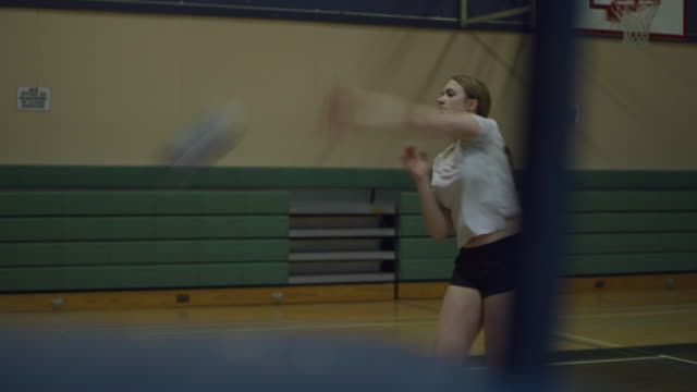 teenage girl hitting volleyball in school gym - volleyball sport stock videos & royalty-free footage