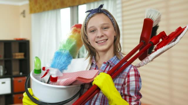 vídeos de stock, filmes e b-roll de hd dolly: menina adolescente segurando um balde de limpeza - pano de pó