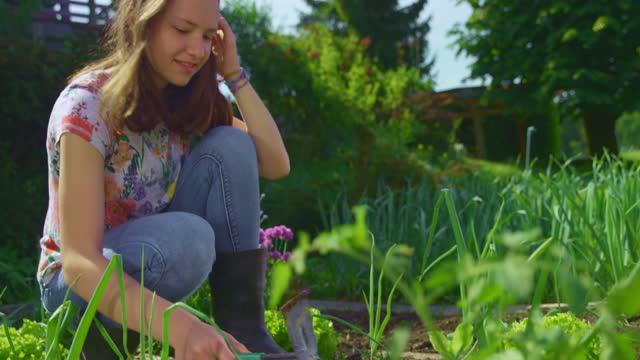 slo mo 10代の少女は小さな庭の鍬を保持し、庭のベッドで働いています - one teenage girl only点の映像素材/bロール